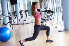 练习一些举重和工作在她的在健身房的二头肌 库存图片