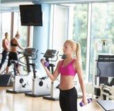 练习一些举重和工作在她的在健身房的二头肌 图库摄影