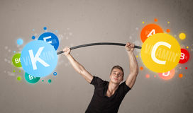 练习五颜六色的维生素举重的肌肉人 图库摄影