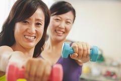 练习在健身房的举重和看照相机的两名成熟妇女 免版税图库摄影