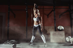 练习在健身房的肌肉年轻健身妇女举重 免版税库存图片