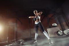 练习在健身房的肌肉年轻健身妇女举重 库存照片