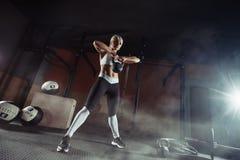 练习在健身房的肌肉年轻健身妇女举重 库存图片