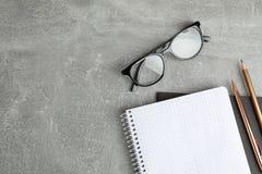 习字簿、玻璃和铅笔在灰色桌上 库存照片