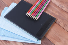 习字簿、铅笔和片剂木表面上 免版税库存图片