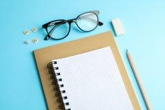 习字簿、铅笔和玻璃在颜色背景 库存图片