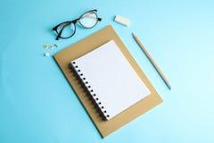 习字簿、铅笔和玻璃在颜色背景 图库摄影