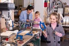 练习技能的快乐的女孩在木雕刻 免版税图库摄影