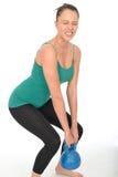 练习5kg水壶响铃举重的可爱的健康少妇 免版税图库摄影