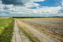 乡下公路、被犁的领域和云彩在天空 免版税库存照片