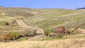 乡下公路和红色谷仓和农场 库存照片