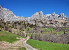 乡下公路在Leukerbad村庄邻里早期的春天的,瓦雷兹,瑞士的小行政区 免版税库存照片