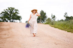 乡下公路的妇女有花的 库存照片