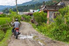 乡下公路的摩托车骑士在山村在Pokh 免版税库存照片