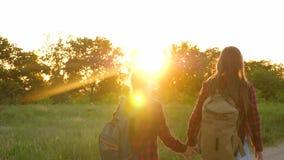 乡下公路的旅游女孩 徒步旅行者女孩,青少年的女孩旅行并且握手 儿童旅客 有背包的女孩 股票录像