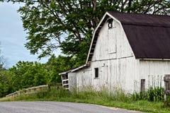 乡下公路的白色谷仓 库存照片