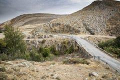 乡下公路通过一座岩石和干燥山 图库摄影