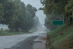 乡下在雾的倾斜路与在路旁的一个路标 免版税库存图片