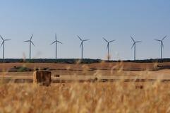 乡下的农田有秸杆大包和风轮机的在背景中 免版税库存照片