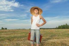 乡下路的快乐的少年旅行者 免版税库存照片