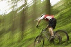 乡下轨道的被弄脏的骑自行车者 库存图片