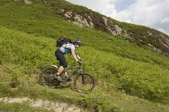 乡下轨道的骑自行车者 免版税库存图片