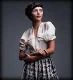 乡情。减速火箭的服装的精妙的被称呼的妇女有时髦的结辨的发型的 免版税库存照片