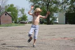 年轻乡村男孩在农场跳并且使用 库存照片