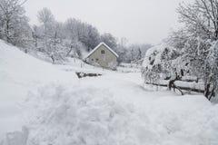 乡间别墅在随风飘飞的雪站立 库存照片