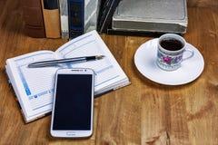 书、一杯咖啡,与笔的一本日志和在t的一个智能手机 免版税库存照片
