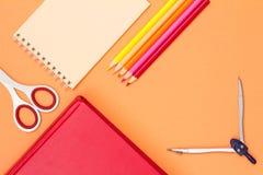书、剪刀、笔记本、颜色铅笔和指南针在桃红色后面 免版税库存照片