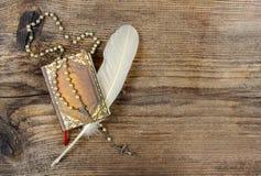 书、念珠和羽毛在木头 库存照片