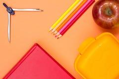 书、指南针、颜色铅笔、红色苹果和午餐盒在桃红色ba 免版税库存图片
