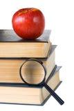书、放大镜和红色苹果 免版税库存照片