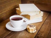 书、曲奇饼和茶在木背景的 免版税库存照片