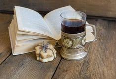 书、曲奇饼和茶在沿海航船在木背景 库存图片