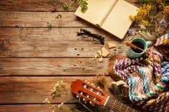 书、毯子、咖啡和经典吉他在木头 免版税图库摄影