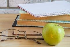 书、苹果计算机、笔记本、放大镜和笔在木桌上 回到概念学校 图库摄影