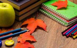 书、铅笔、笔记本、秋天红色叶子和绿色苹果 免版税库存图片