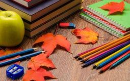 书、铅笔、笔记本和苹果在桌上 免版税图库摄影