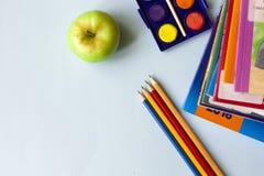 书、铅笔和苹果在桌上 免版税图库摄影