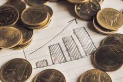 书写凹道在笔记本纸的企业图表与硬币事务 库存照片