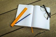 书写,空白的笔记本的黄色统治者写您的笔记和gl 免版税库存图片