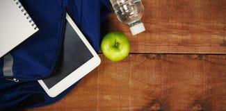 书包用苹果和在桌上的数字式片剂 库存图片
