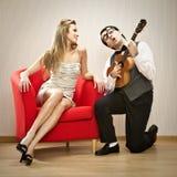 书呆子人男朋友戏剧尤克里里琴他的女朋友的爱情歌曲为情人节 免版税库存照片