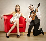 书呆子人男朋友戏剧尤克里里琴他的女朋友的爱情歌曲为情人节 免版税图库摄影