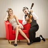 书呆子人男朋友戏剧尤克里里琴他的女朋友的爱情歌曲为情人节 库存图片