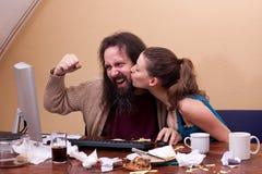 书呆子庆祝成功在计算机,妇女的亲吻 图库摄影