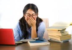 书呆子玻璃工作的年轻甜和愉快的亚裔韩国学生女孩快乐在书桌上的手提电脑有堆的书 库存图片