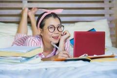 书呆子玻璃的在家学习卧室的年轻逗人喜爱和愉快的讨厌的亚裔韩国学生少年女孩和头发丝带坐  库存照片
